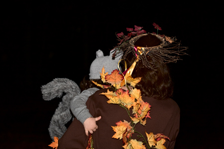 A squirrel climbs a tree to go trick-or-treating